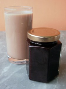 Jar of homemade chocolate syrup with a glass of chocolate milk
