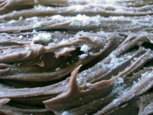 Closeup of chocolate buttercream icing on a chocolate yule log.
