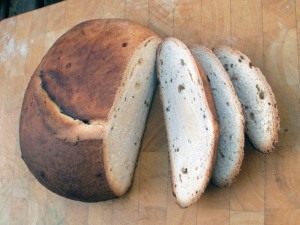 Loaf of York mayne bread with several slices cut from it.