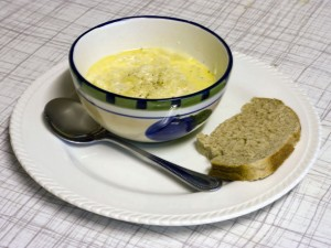 A bowl of cauliflower cheese soup with a spoon and a slice of bread