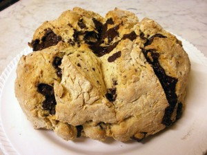 Round loaf of white Irish soda bread with dark chocolate