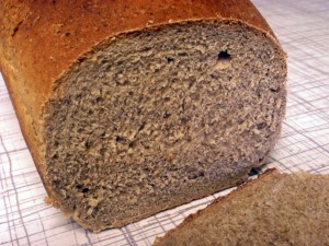A loaf of honey rye bread that has been sliced, showing the crumb.