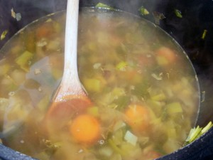 Pot of leeks, carrots and potatoes cooking in stock.