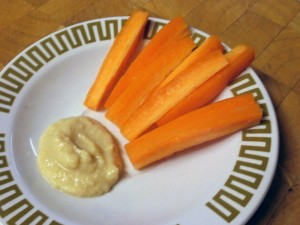 A plate with homemade hummus and sticks of raw carrot.