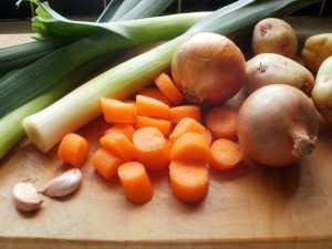 Leeks, carrots, onions, potatoes and garlic in a chopping board.