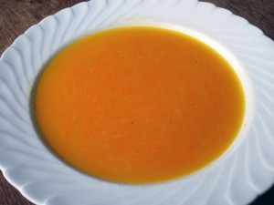 A white bowl full of carrot and orange soup