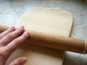 Puff pastry being rolled out with a rolling pin