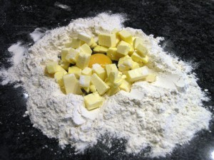 An egg and cubed butter, surrounded by plain flour