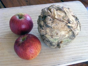 A celeriac and two red apples on a chopping board